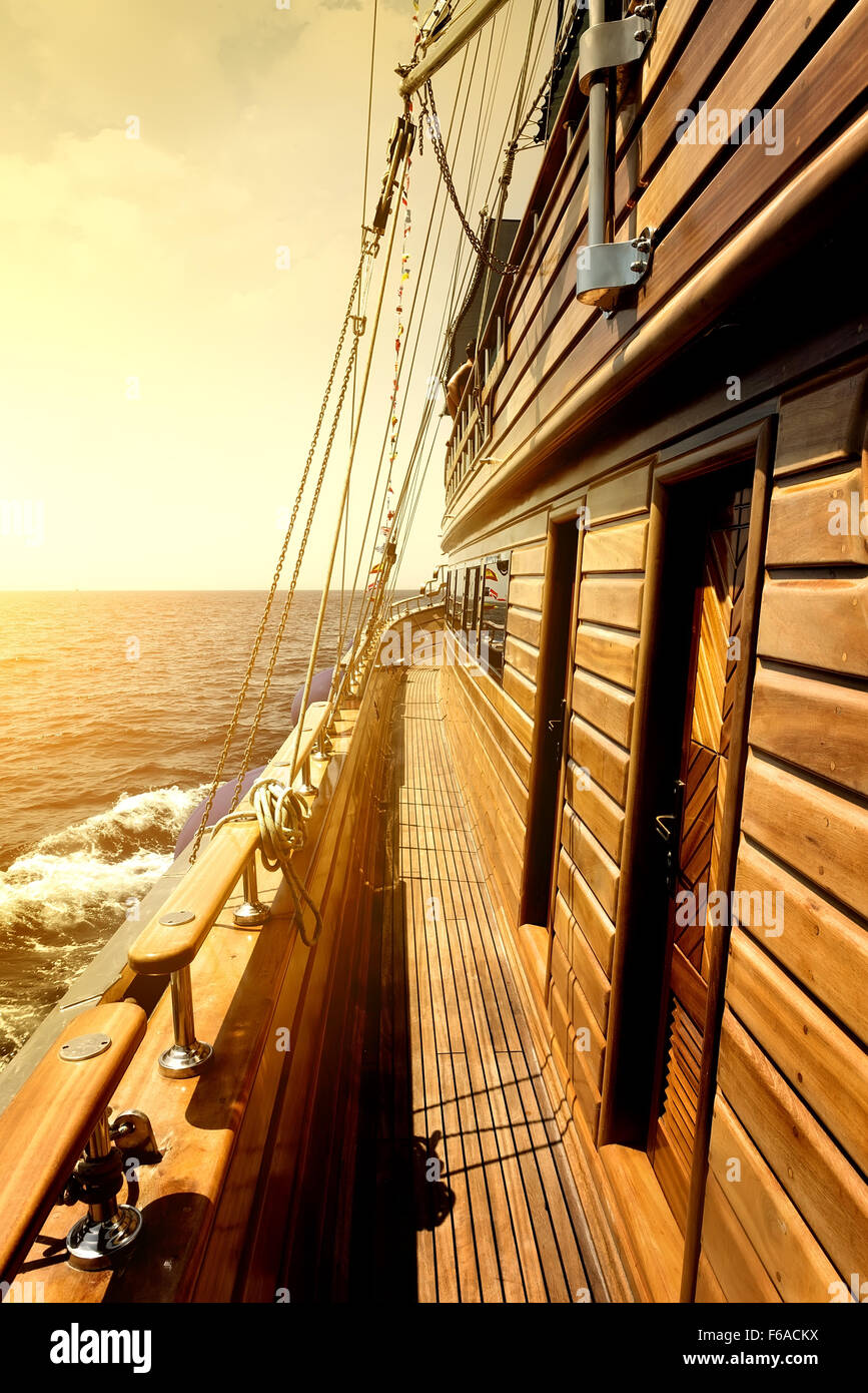 Wooden sailboat in sea at the bright sunrise - Stock Image