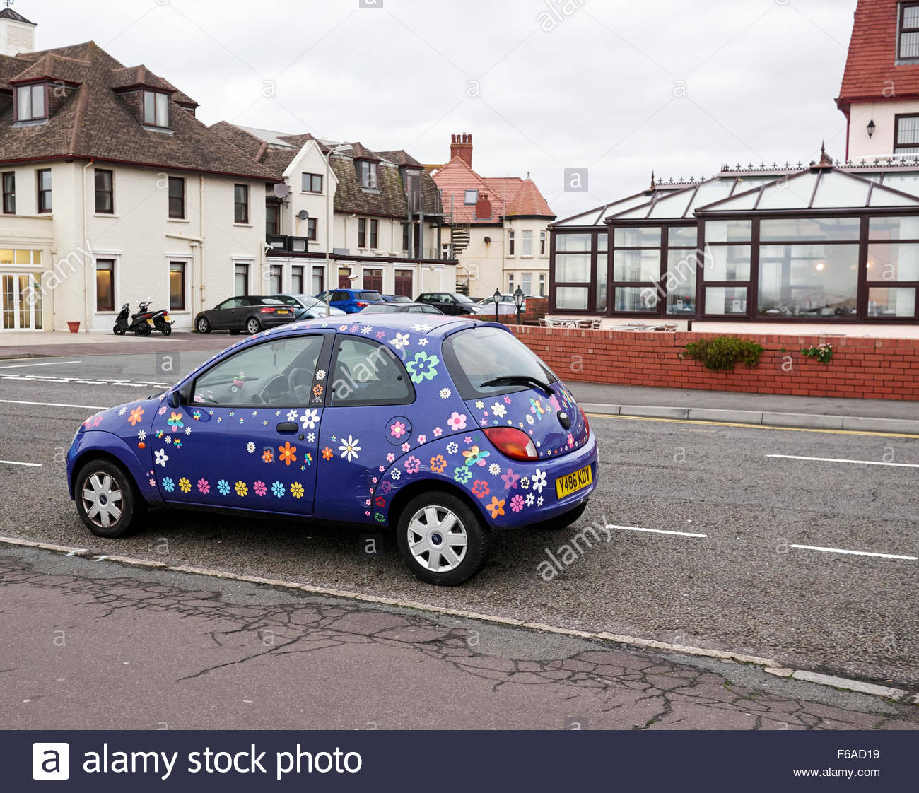A blue ford KA motorcar covered in colourful flower transfers - Stock Image