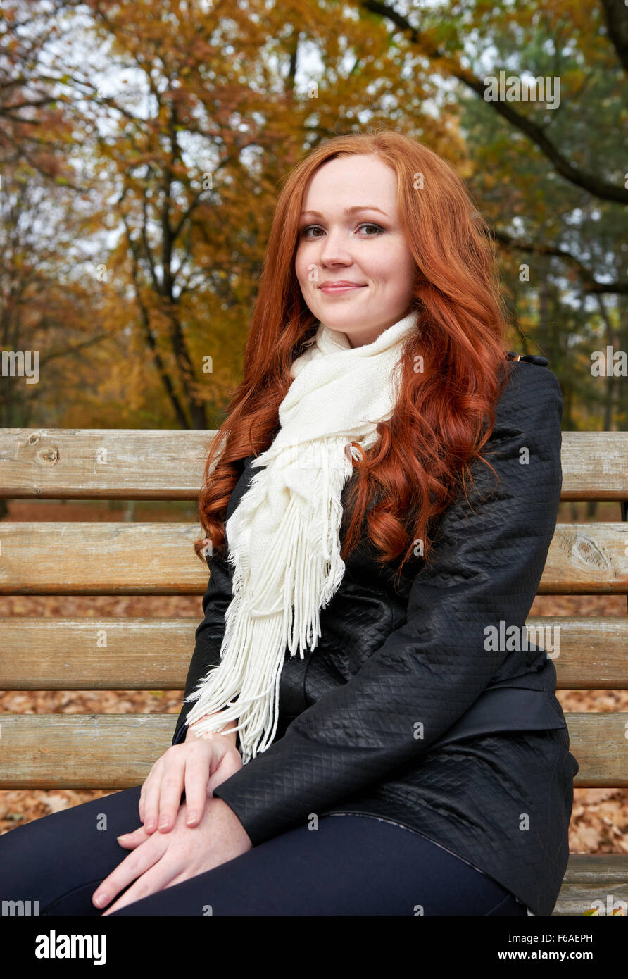 redhead girl portrait in city park, fall season - Stock Image