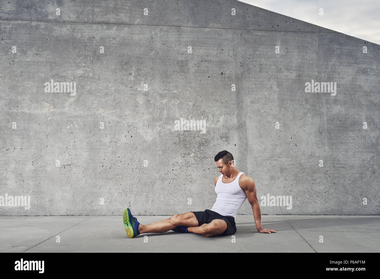 Fitness athlete man relaxing and stretching muscles and legs wearing a white tank top, well build, copy space - Stock Image
