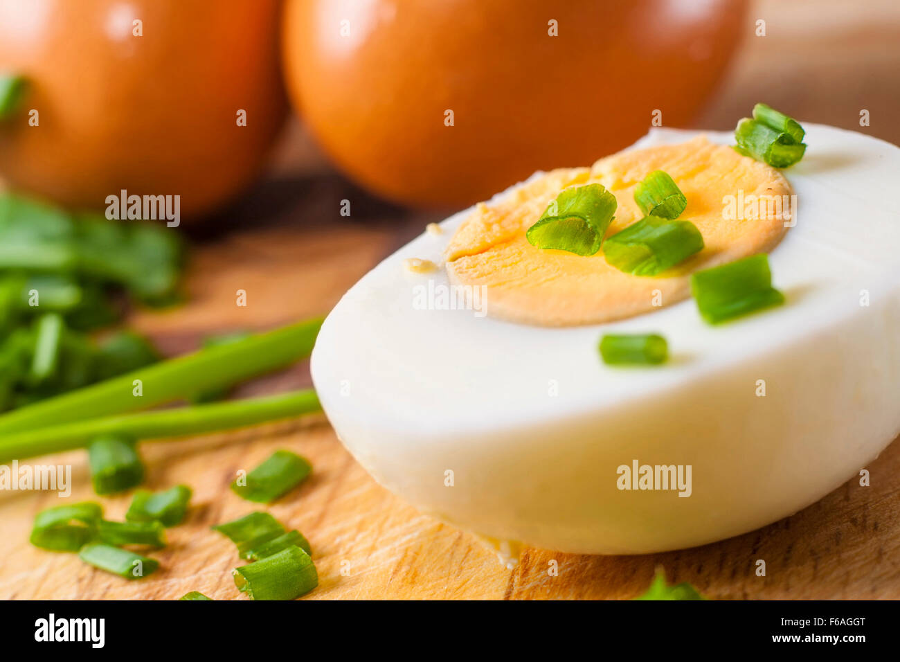 Half of boiled egg  prepared on cutting board with sliced chive and two whole eggs in background Stock Photo