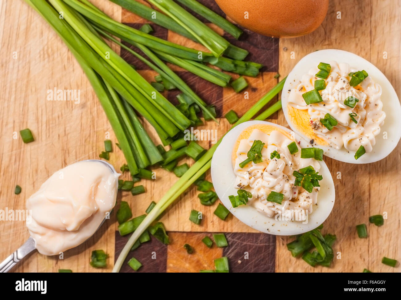 Two halves of boiled eggs with mayonnaise and sliced chive prepared on cutting - Stock Image