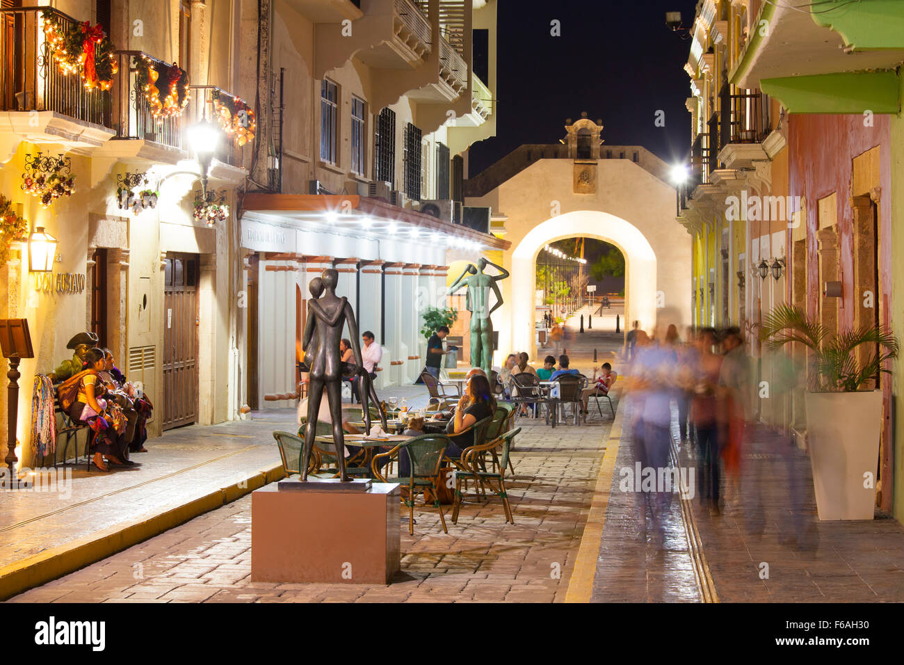 Night scene of outdoor cafes and street strollers in Campeche, Mexico. - Stock Image