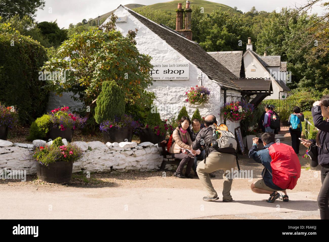 Tourists taking photographs outside traditional Scottish cottage shop in Luss,  Scotland, UK - Stock Image