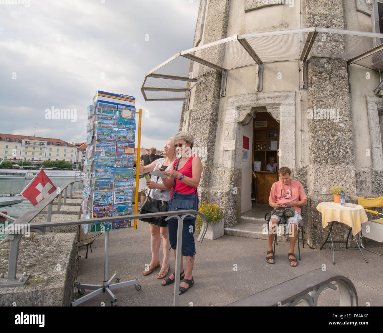 Lindau Lighthouse - tourists choosing and writing postcards at the lighthouse at the entrance to Lindau harbour, - Stock Image