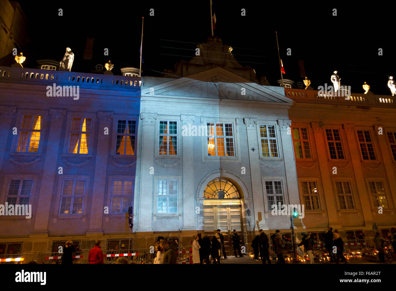 Copenhagen, Denmark, 15th November, 2015. Thousands of people in Copenhagen show their solidarity and sympathy with the French people outside the French Embassy in Copenhagen after last Friday's terror attacks in Paris. The huge amount of flowers and messages still grows this Sunday evening. Kongens Nytorv in Copenhagen is lit by the colours of the French Tricolore projected on the building of the still crowded French Embassy after a day of official memorial events and spontaneous actions of sympathy and solidarity. Credit:  Niels Quist/Alamy Live News Stock Photo