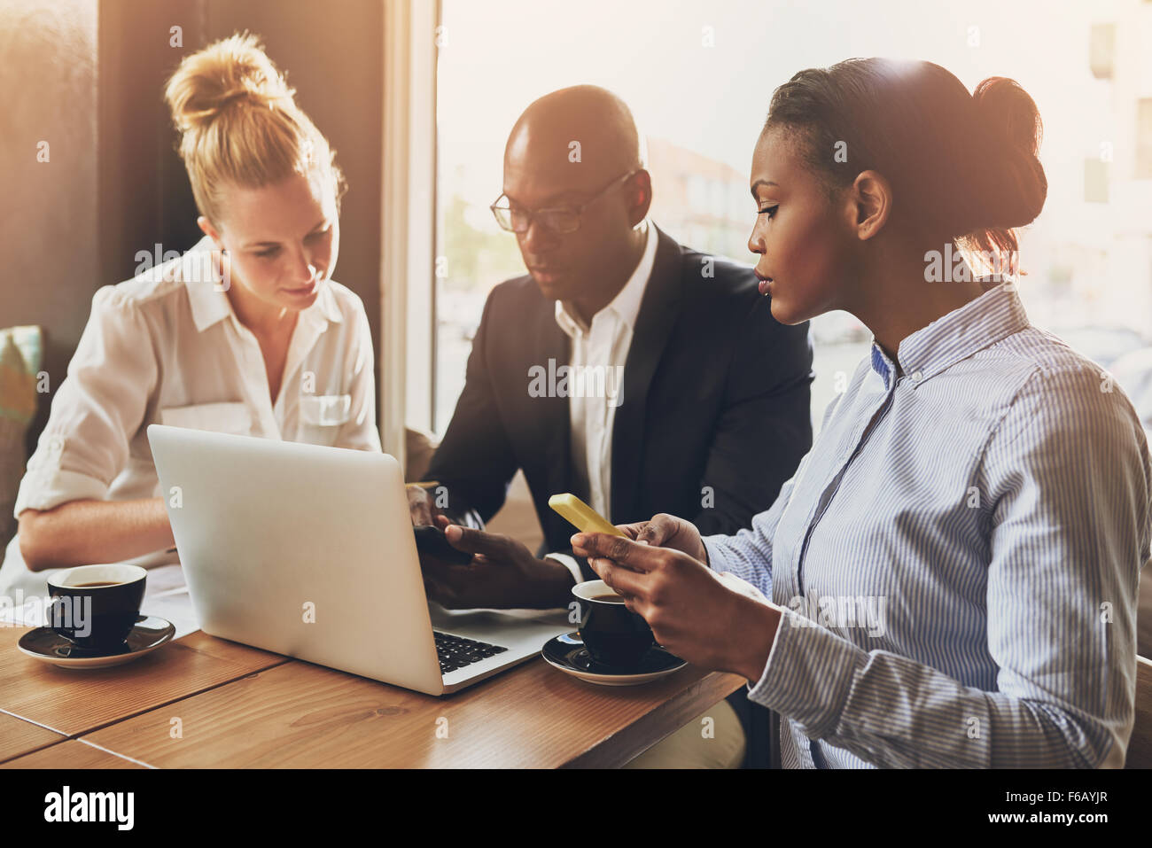 Multi ethnic entrepreneurs planning their work using laptop and cell phone - Stock Image