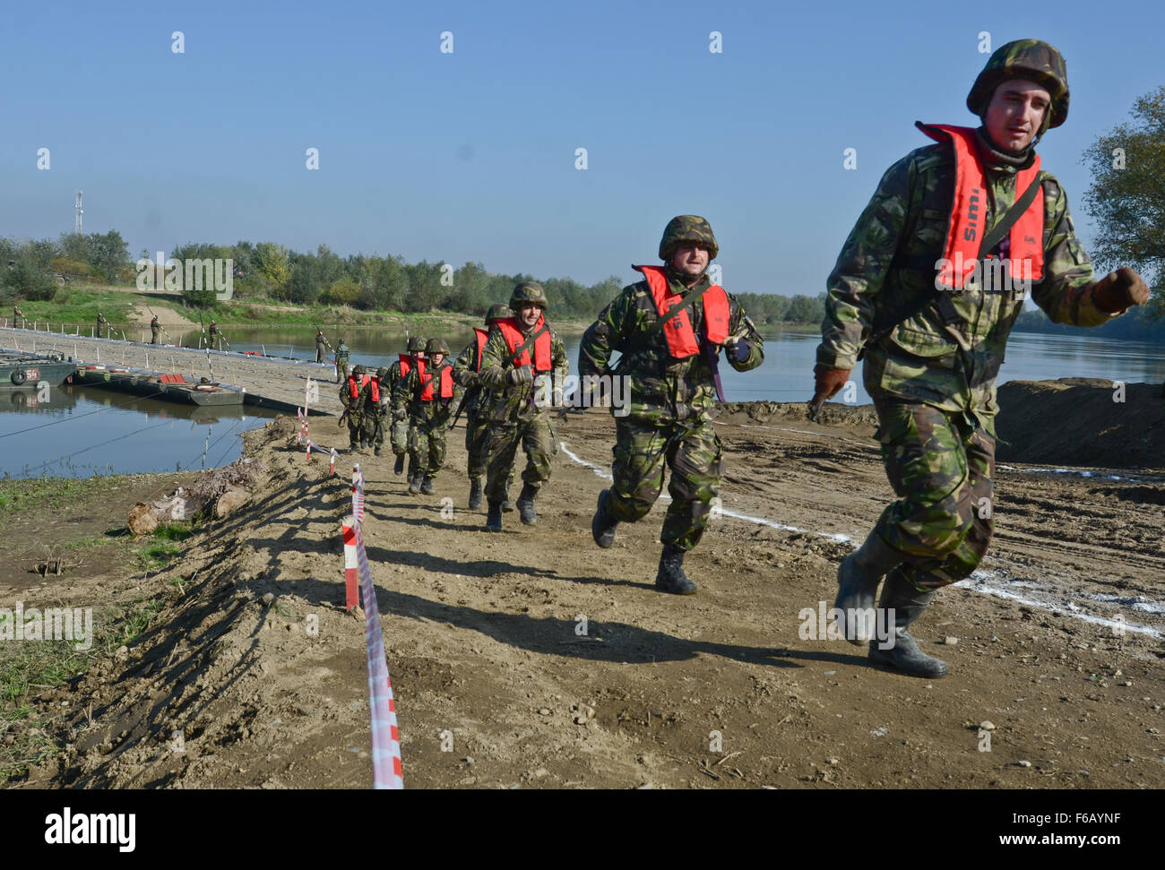 Romanian Soldiers run up the hill in a single file near the Mures River as part of the defense demonstration during - Stock Image