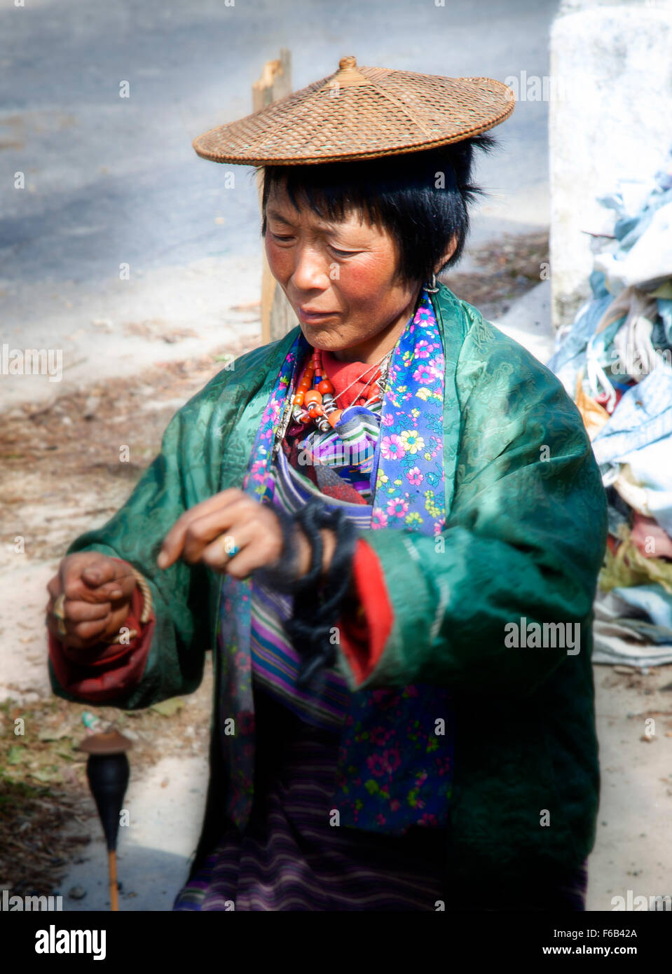 A woman spins yak wool into yarn in the high mountains of Bhutan. - Stock Image