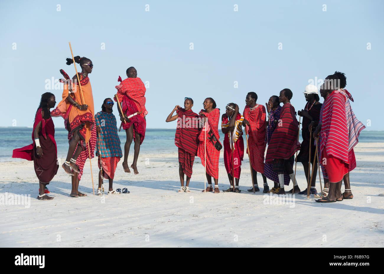 Maasai tribesmen perform the jumping dance, or adumu on the beach on the island of Unguja in the Zanzibar archipelago. - Stock Image