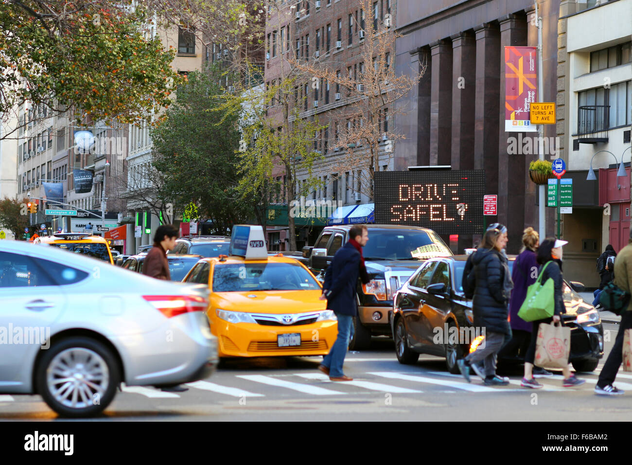 An electronic sign flashes Drive Safely near a New York City intersection - Stock Image