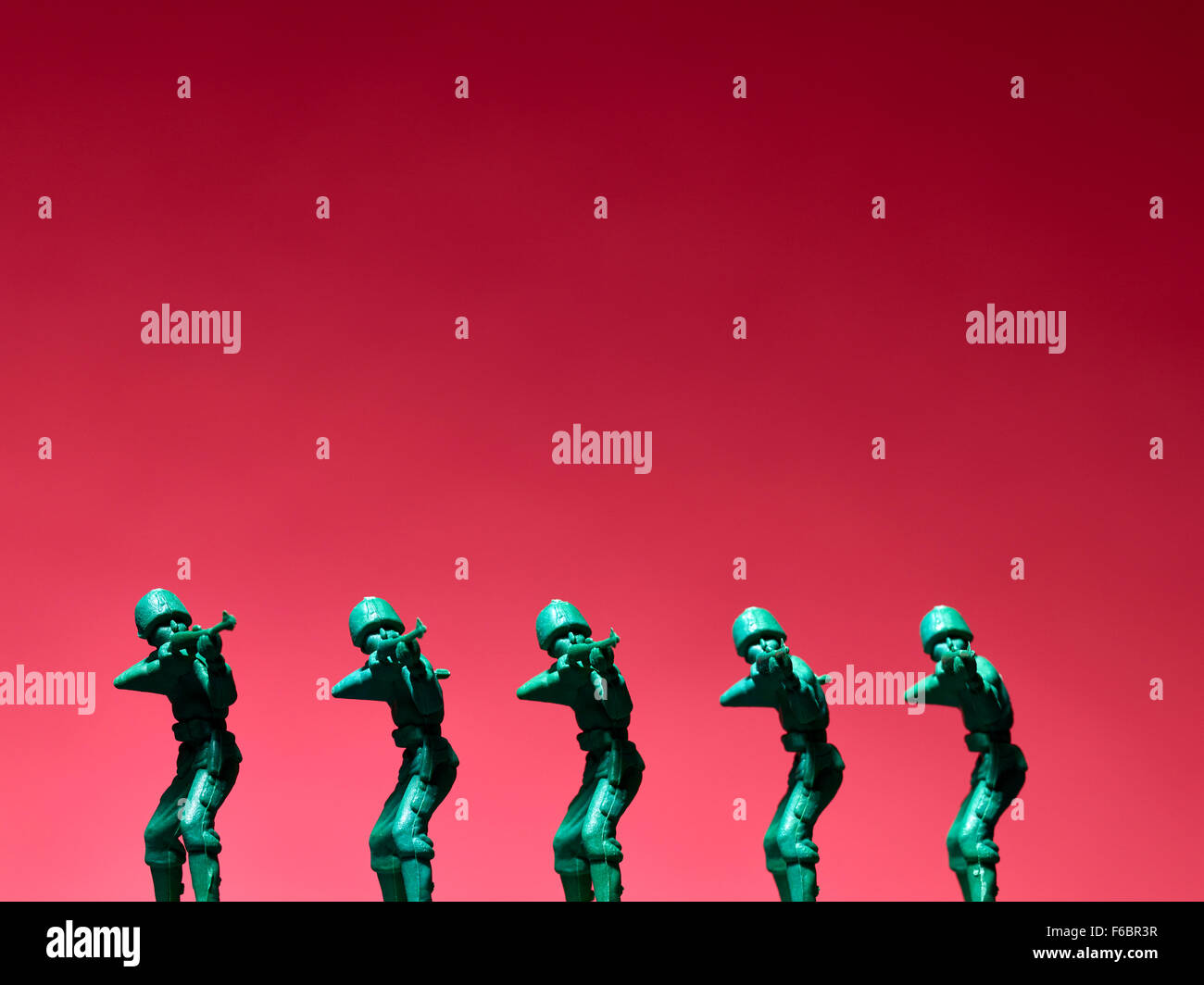 Several plastic soldiers in row, red background Stock Photo