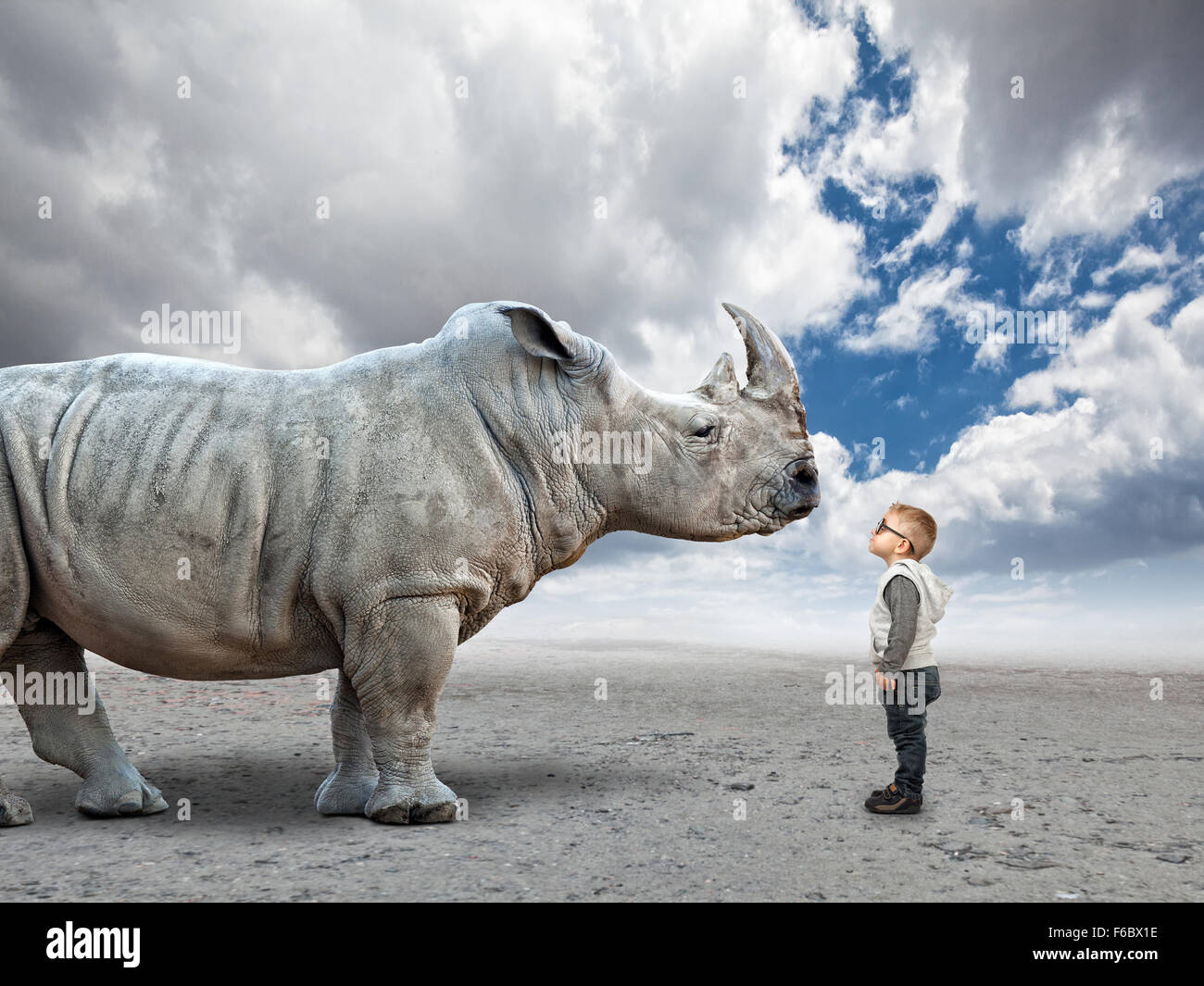 little child and huge rhino with abstract background Stock Photo