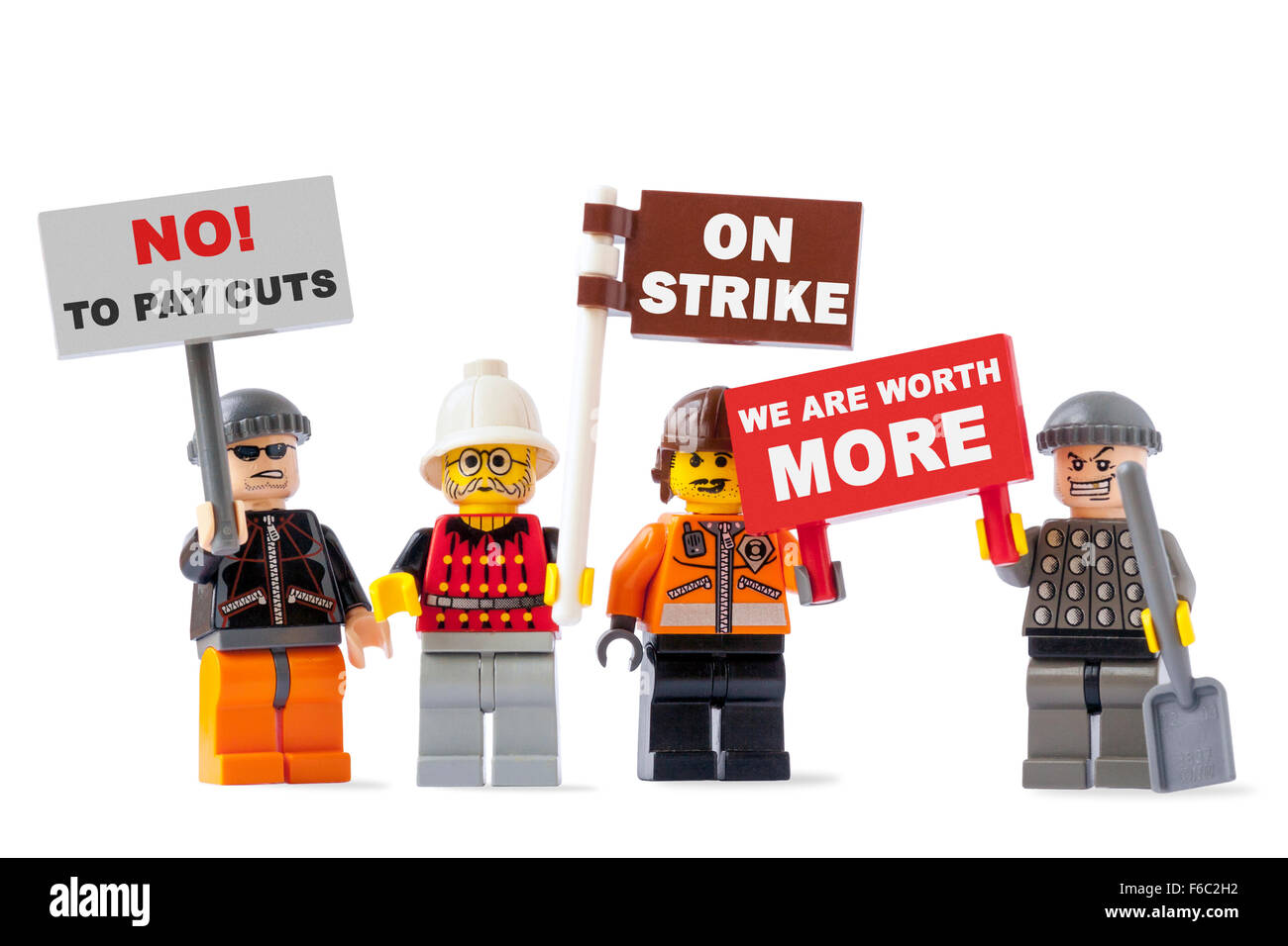 Workers on strike concept with four toy figurines isolated on white background and holding signs with protest messages - Stock Image
