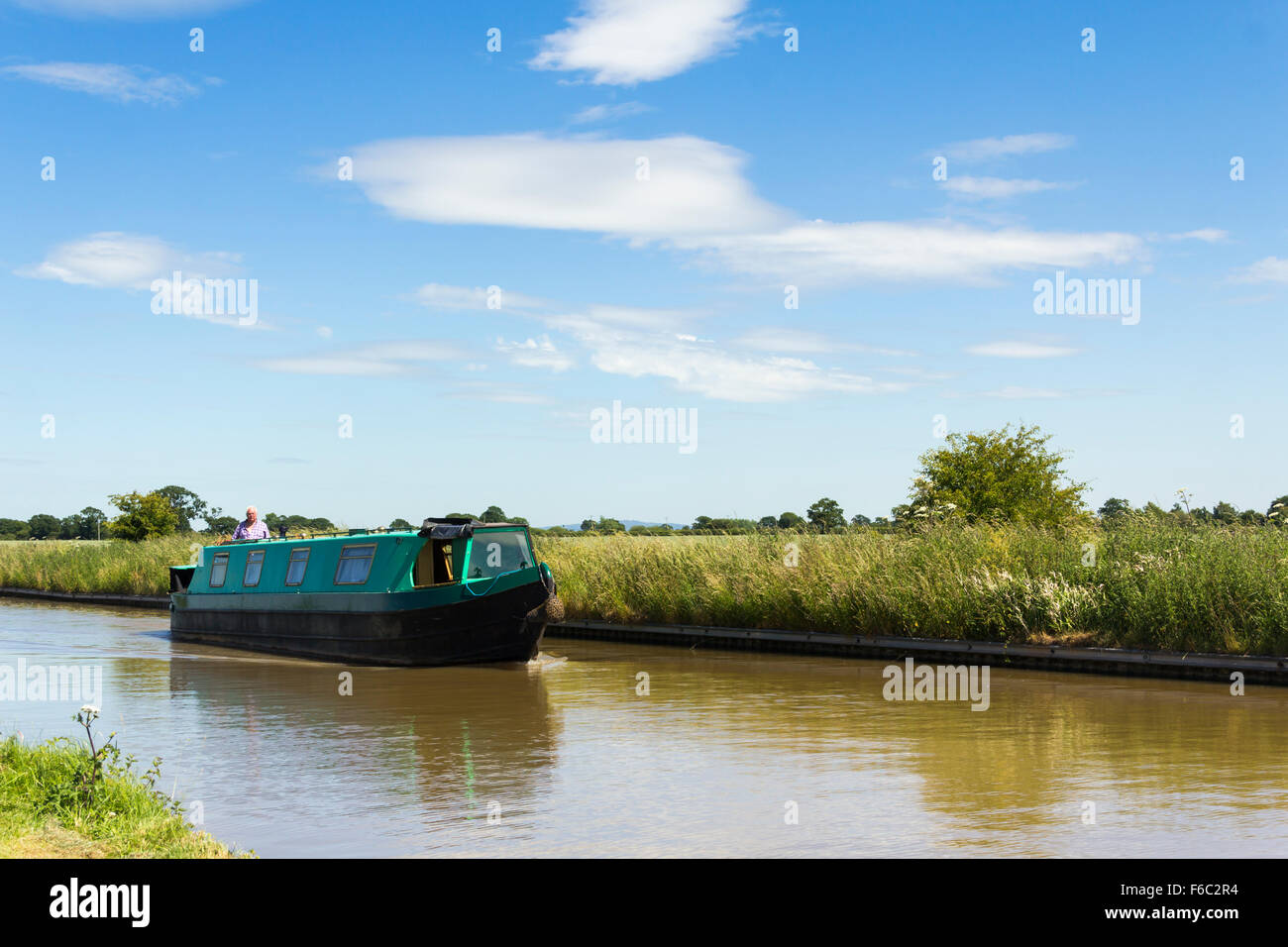 Unidentified houseboat sailing west  on Shropshire Union Canal Middlewich branch near Worleston, Cheshire. - Stock Image