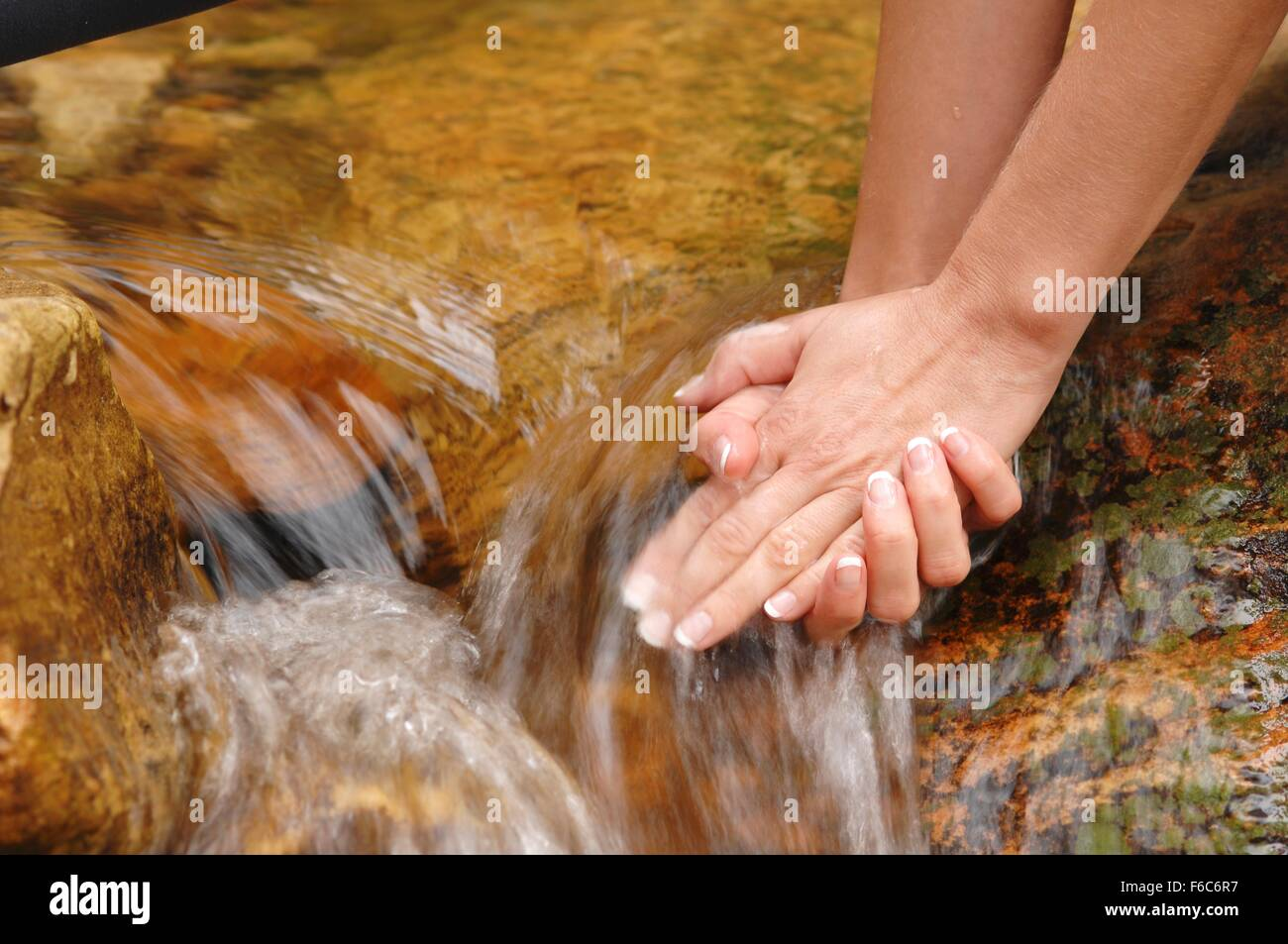 A woman holding her hands under running water - Stock Image