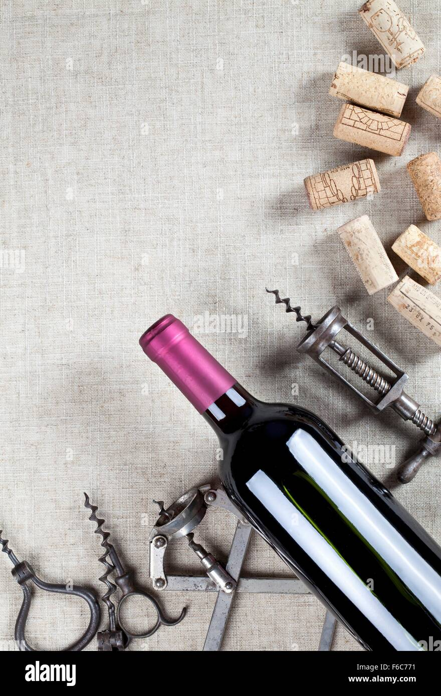 A bottle of red wine, old corkscrews and wine corks - Stock Image