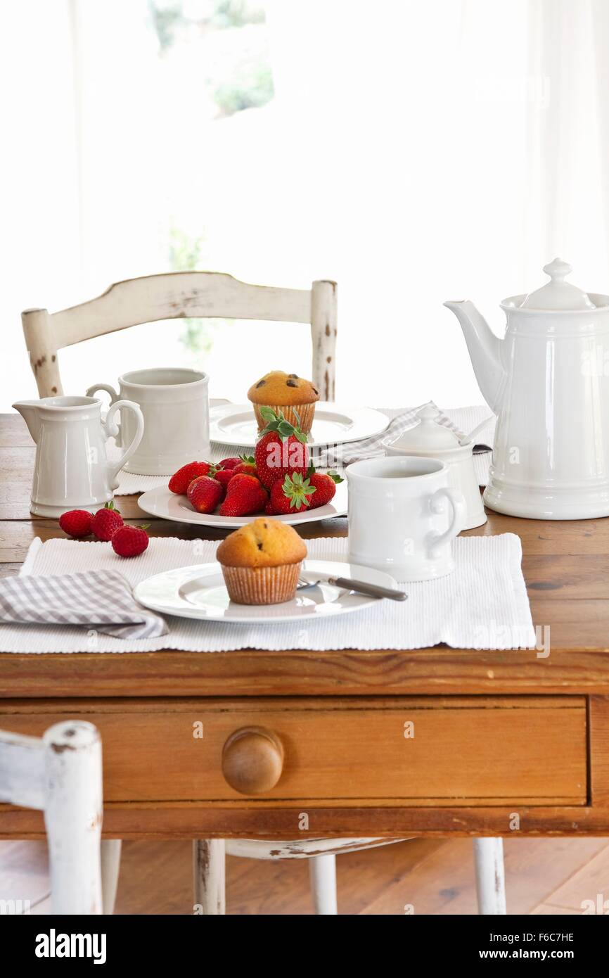 A table laid for coffee with muffins and fresh strawberries - Stock Image