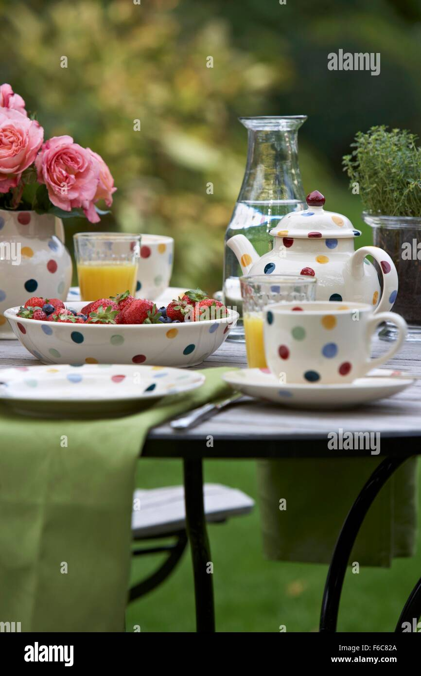 Breakfast laid in a garden with strawberries and orange juice - Stock Image