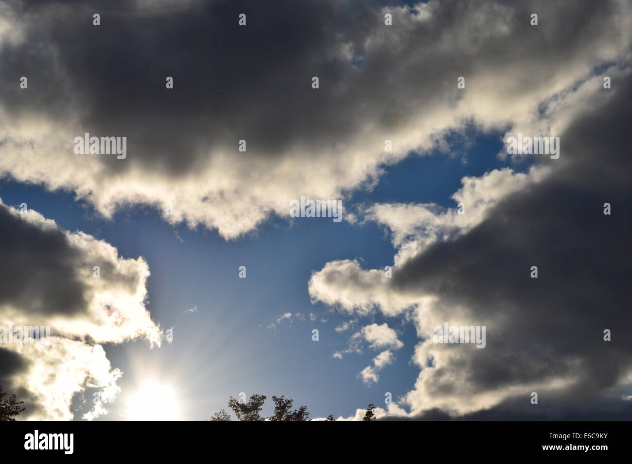 Sun with fluffy clouds - Stock Image