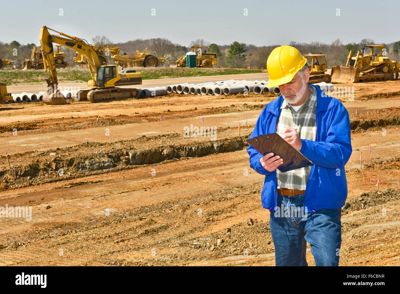 Foreman Keeping Records on Highway Construction Site - Stock Image