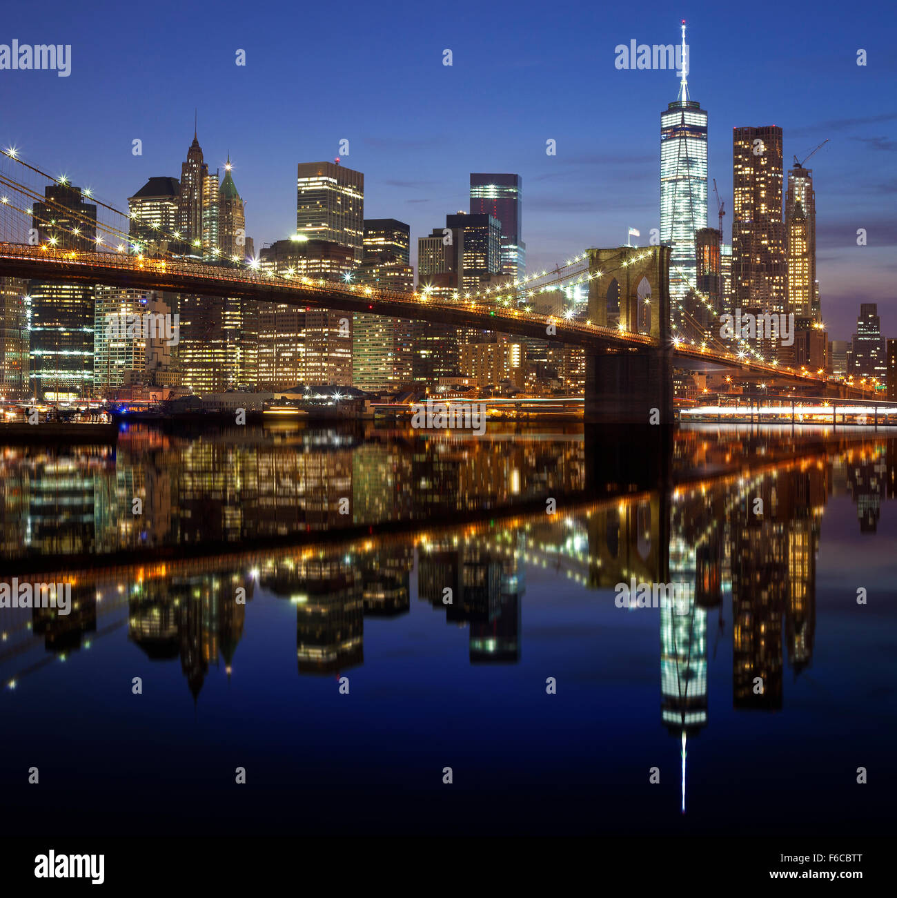 Manhattan waterfront reflected in water at night, New York City, USA. - Stock Image