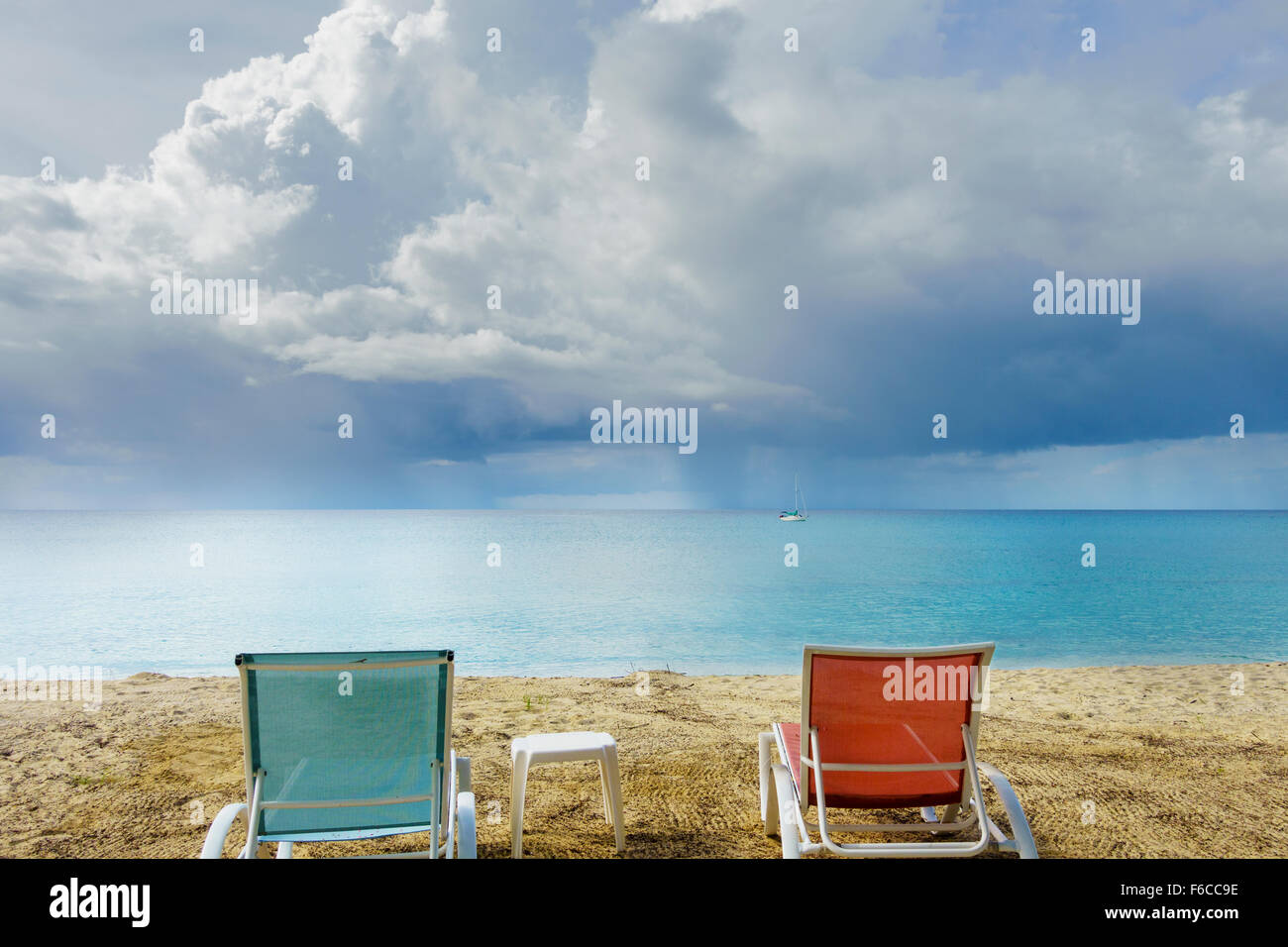 Two empty beach chairs look out on a tropical storm over the Caribbean sea in St. Croix, U.S. Virgin Islands. Stock Photo