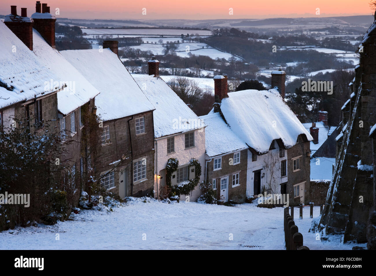 View of Gold Hill at Shaftesbury in Dorset at dusk, coated in snow during a prolonged spell of cold weather. - Stock Image