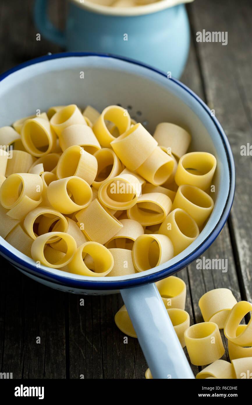 uncooked pasta calamarata in colander - Stock Image