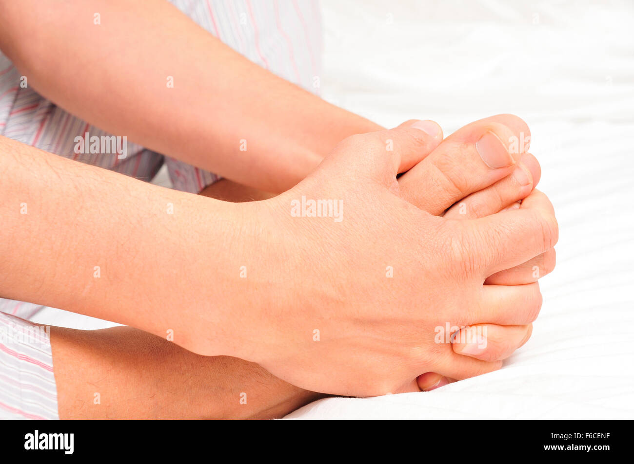 closeup of a young caucasian man in pajamas grabbing his feet with his hands - Stock Image