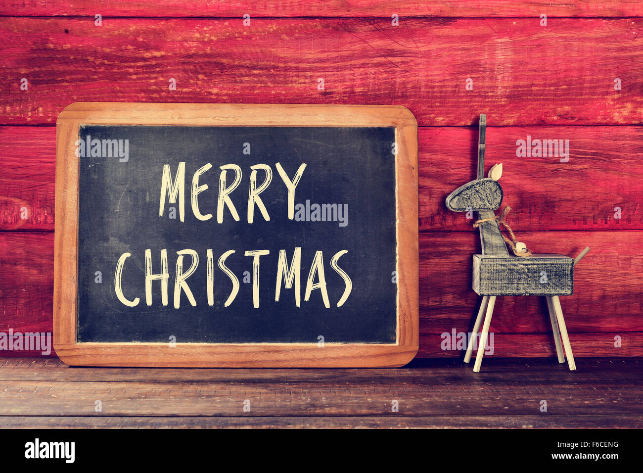 a chalkboard with the text merry christmas written in it and a rustic wooden reindeer placed on a wooden surface - Stock Image