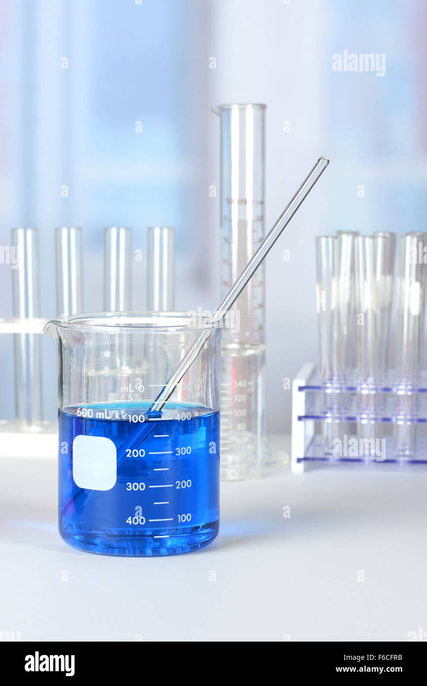 Laboratory glassware with liquids on lab table - Stock Image