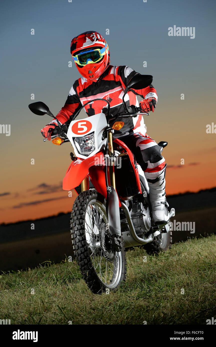 Man riding dirt bike at sunset over grassy area - Stock Image