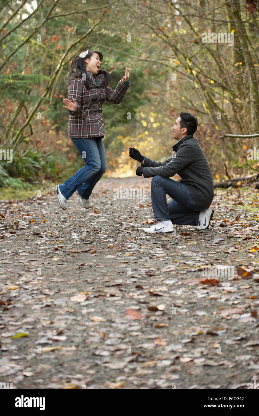 Woman jumps excitingly after engagement proposal - Stock Image