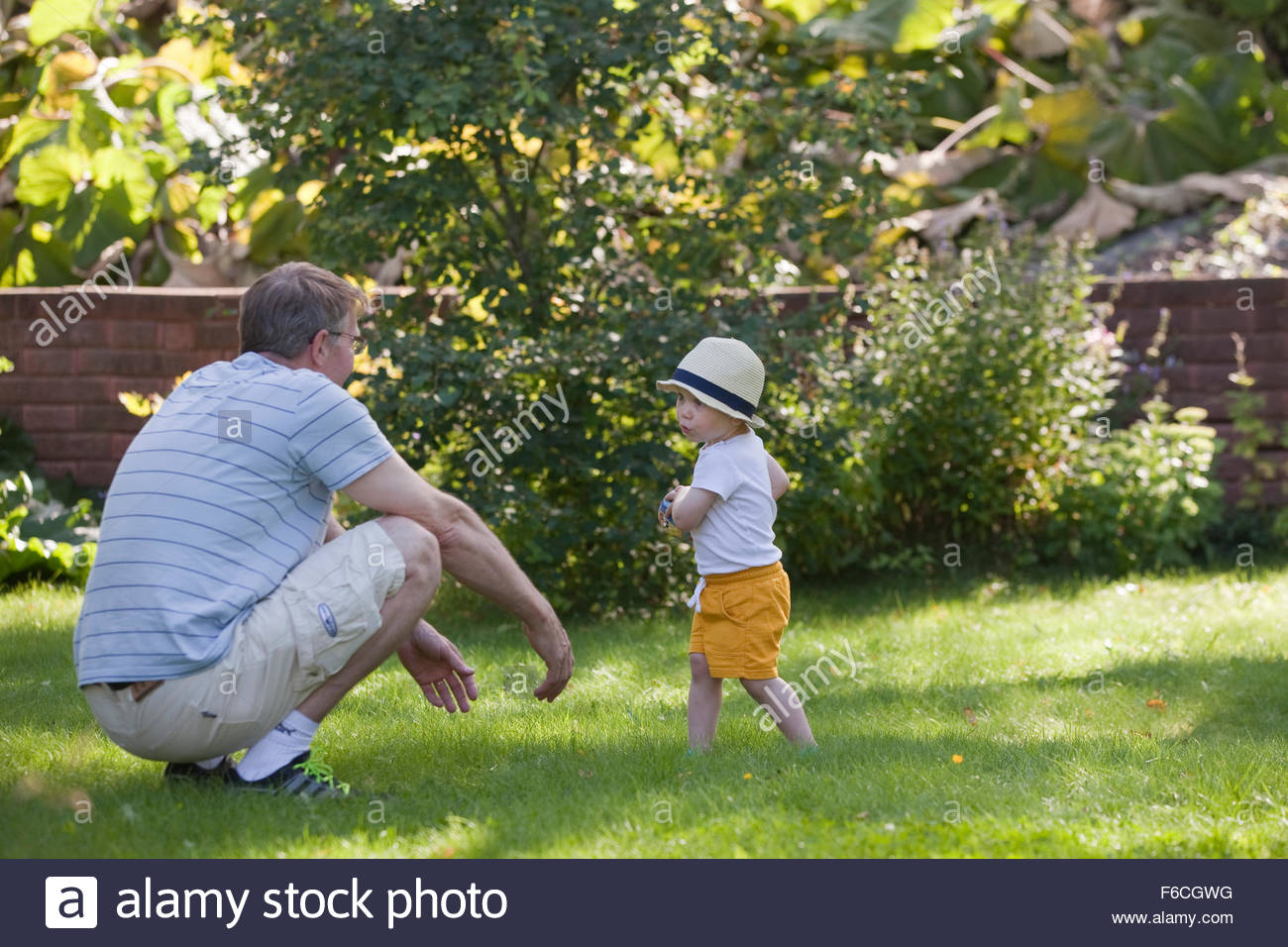 Toddler playing with his grandpa - Stock Image