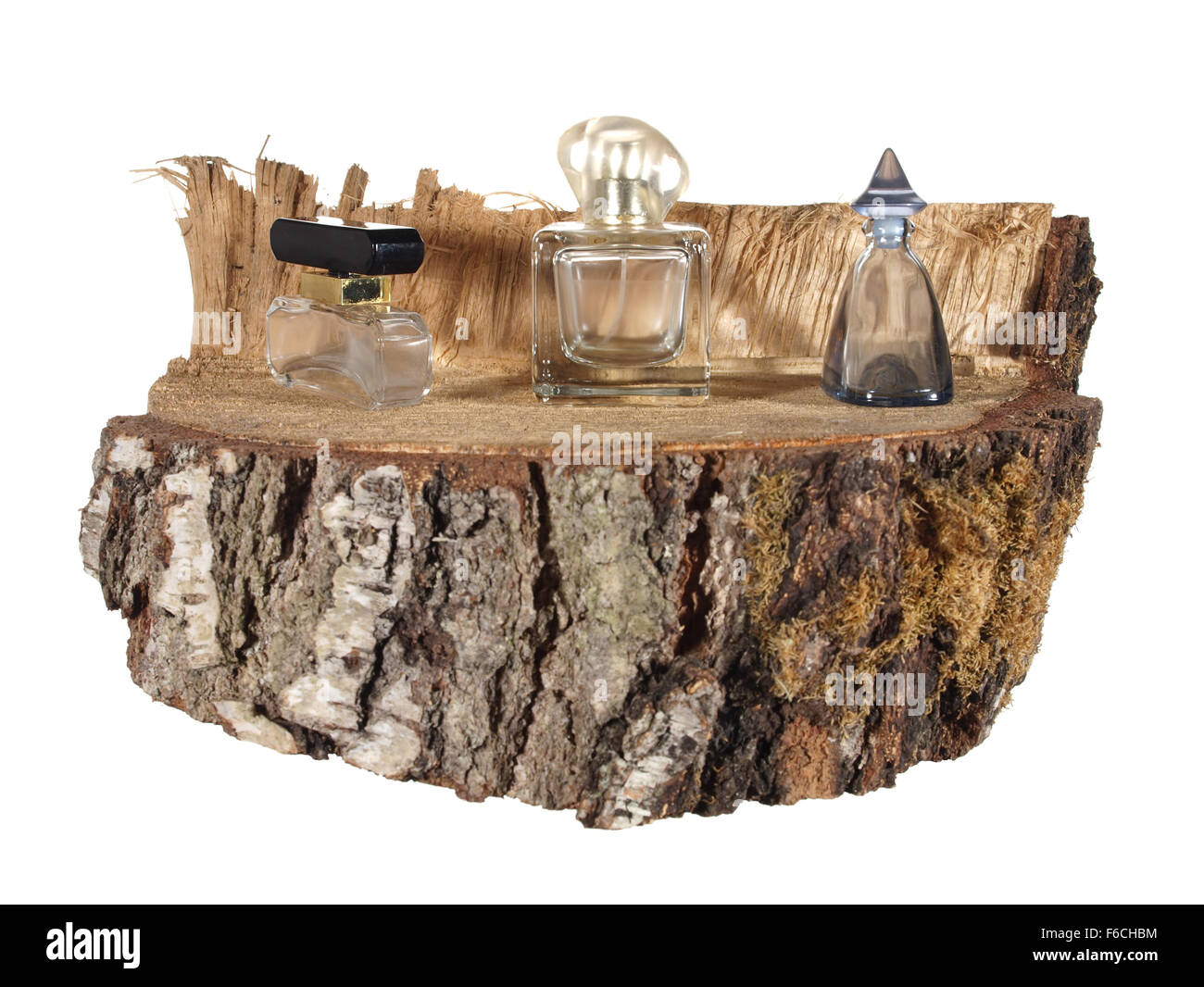 three empty bottle of perfume on a piece of birch trunk isolated on white background. - Stock Image