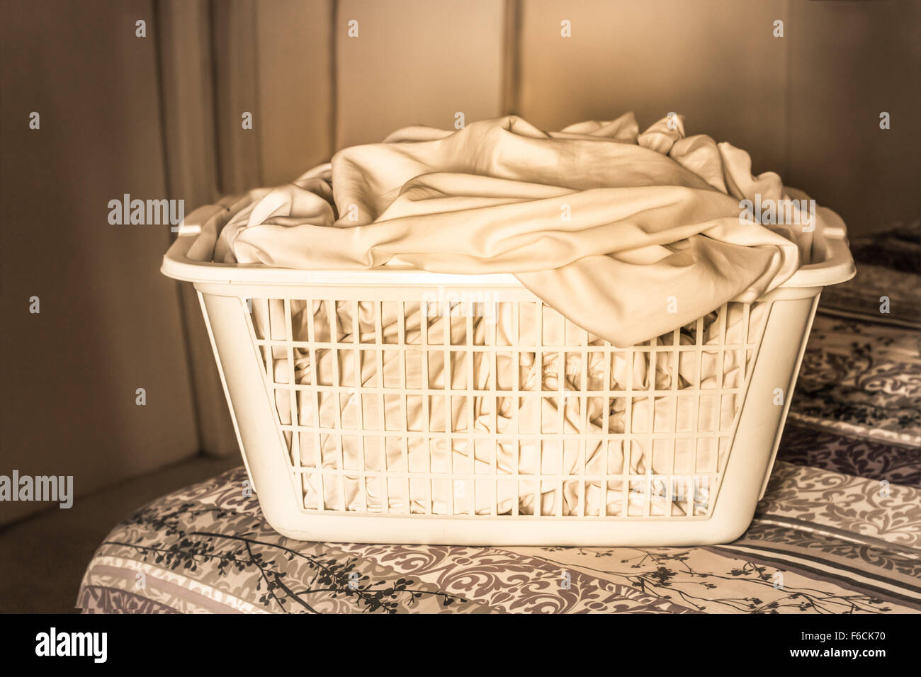 Plastic laundry basket with sheets on bed - Stock Image