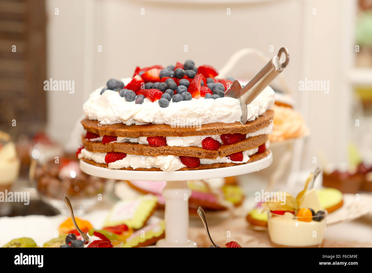 Delicious biscuit cake with strawberries and blueberries on sweet table for wedding party - Stock Image