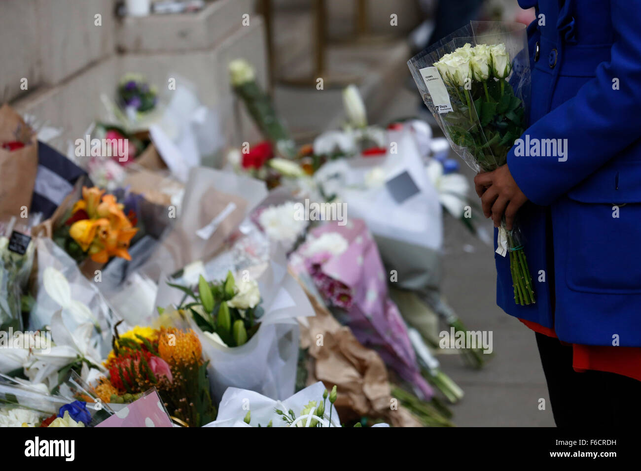 London, UK. 16th Nov, 2015. A woman prepares to lay flowers outside the Embassy of France in London, UK, Monday, Stock Photo