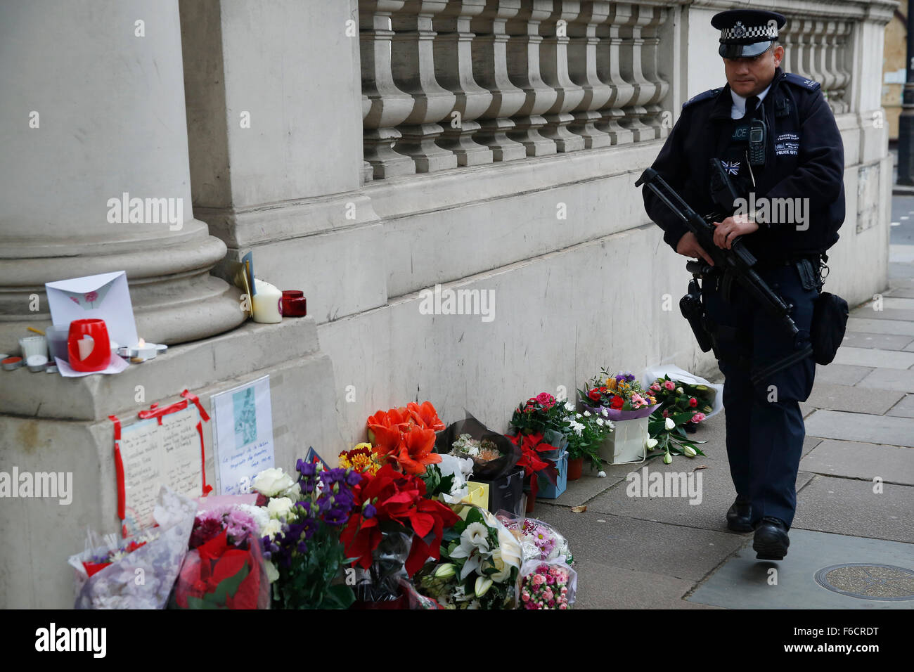 London, UK. 16th Nov, 2015. An armed police officer patrols near flowers, laid for the dead after the shooting in Stock Photo