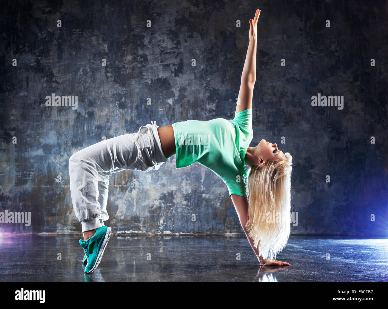 Young woman modern dancer. On dark stone wall background. - Stock Image