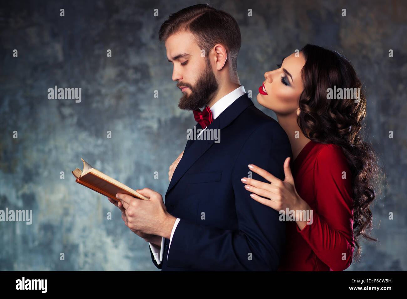 e9fb7a01e305b Young elegant couple in evening dress portrait. Man reading book and woman  trying to attract and embrace him.