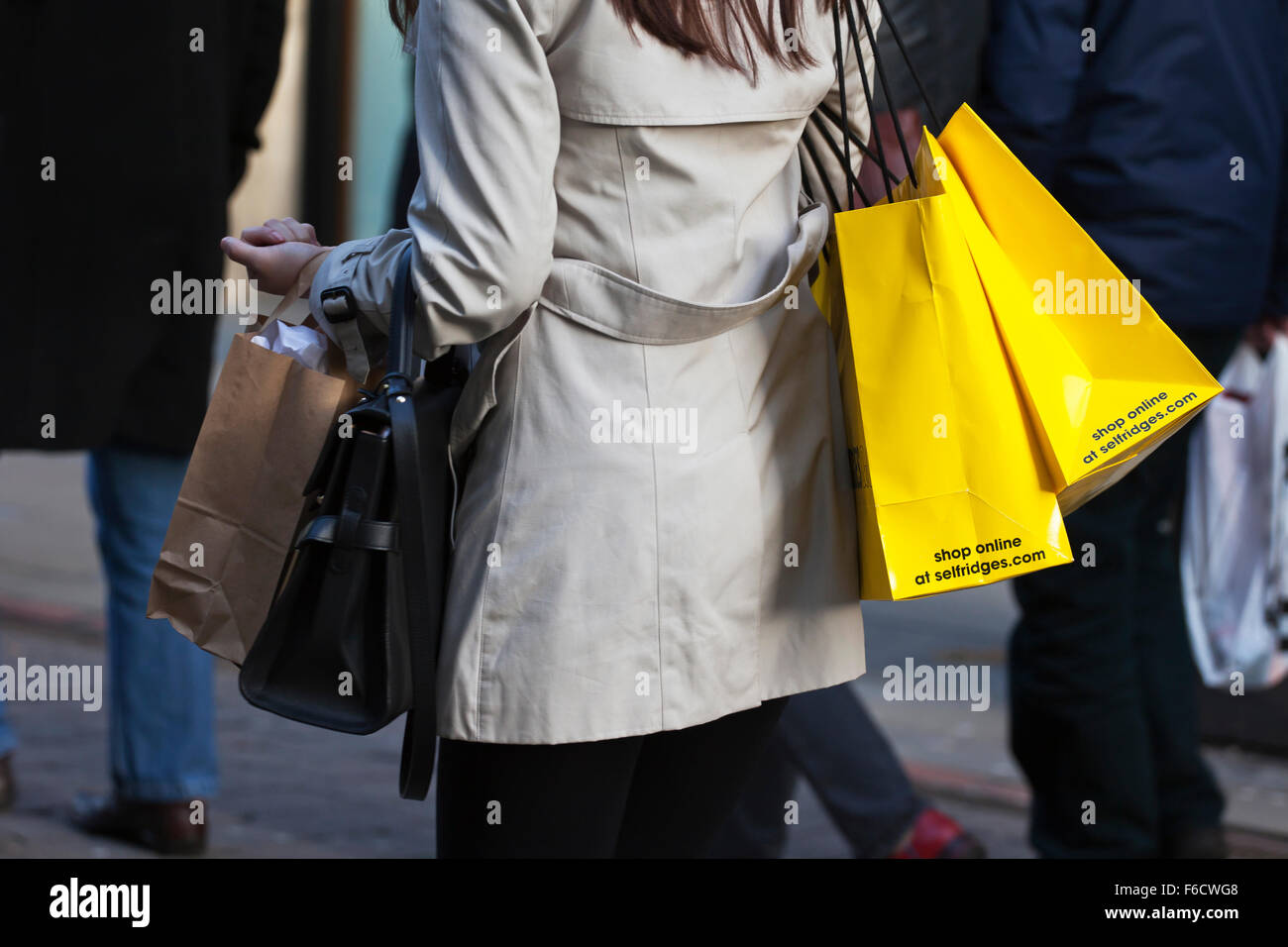 Shop online; A woman carrying yellow multiple branded Selfridges shopping bags on Market St. Piccadilly, Manchester, Stock Photo