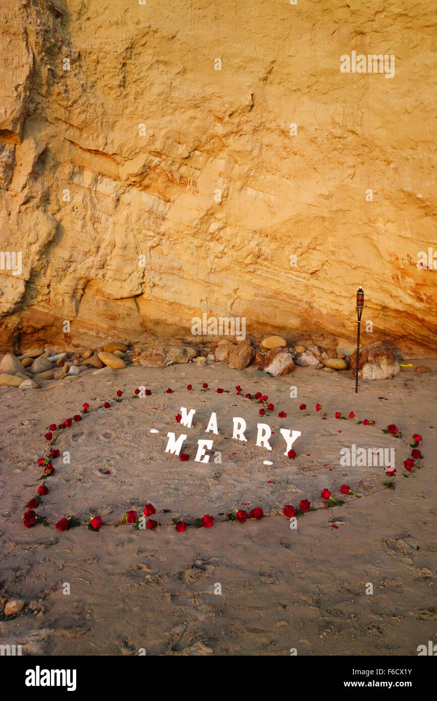 artistic beach marriage proposal from flowers and heart in sand in California central coast - Stock Image