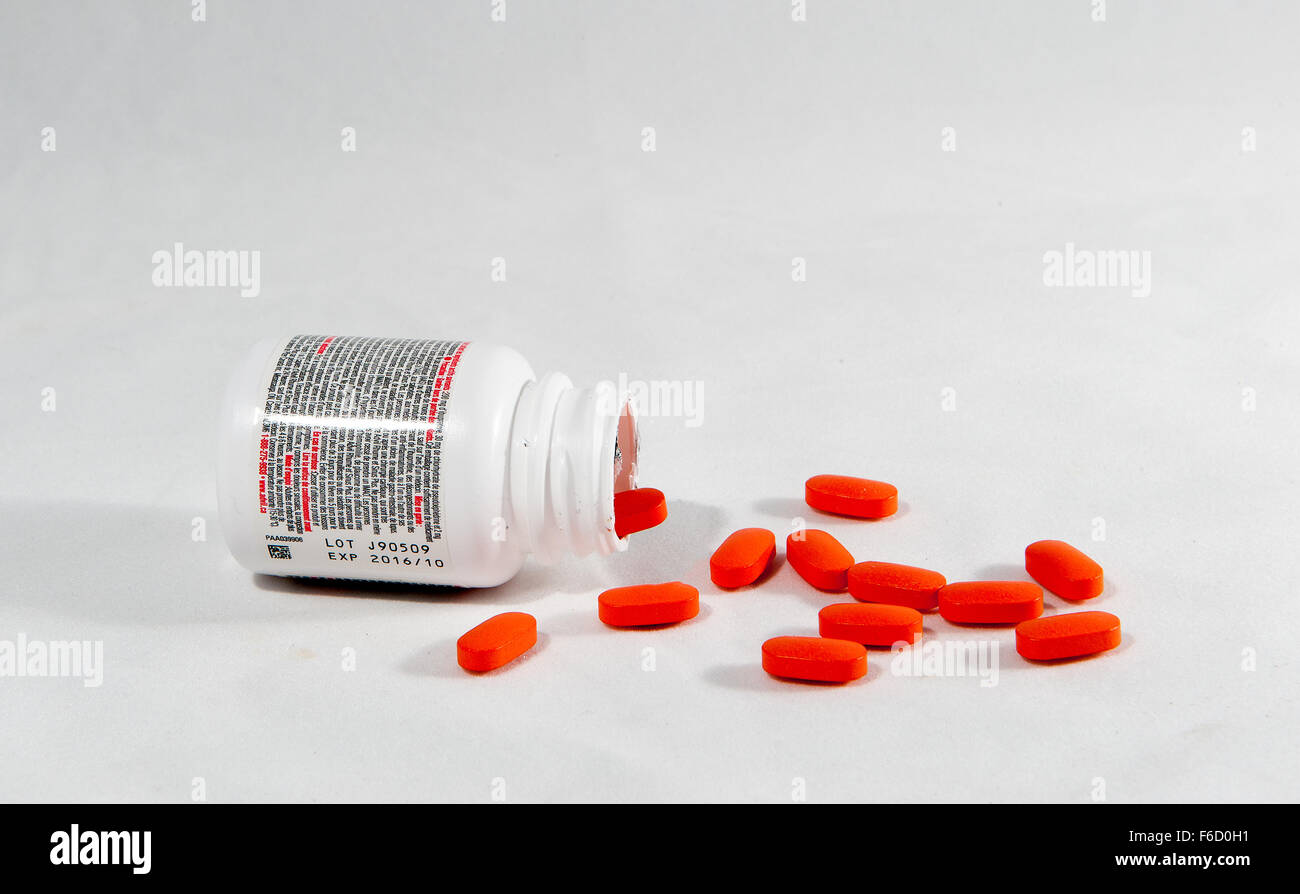 A container of Advil on it's side and spilled tablets against a white background - Stock Image