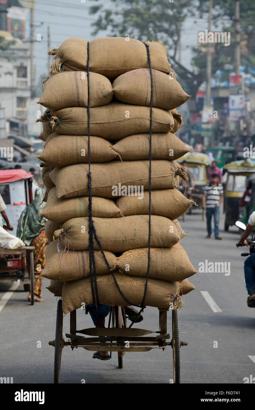 BANGLADESH Tangail, worker transport paddy in jute bags with bicycle rickshaw from rice mill near Kalihati / BANGLADESCH - Stock Image