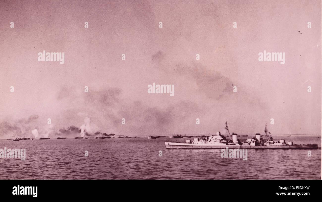 712. Italy. Anzio landings. Cruiser bombarding enemy shore positions as landing craft close into the beaches Stock Photo