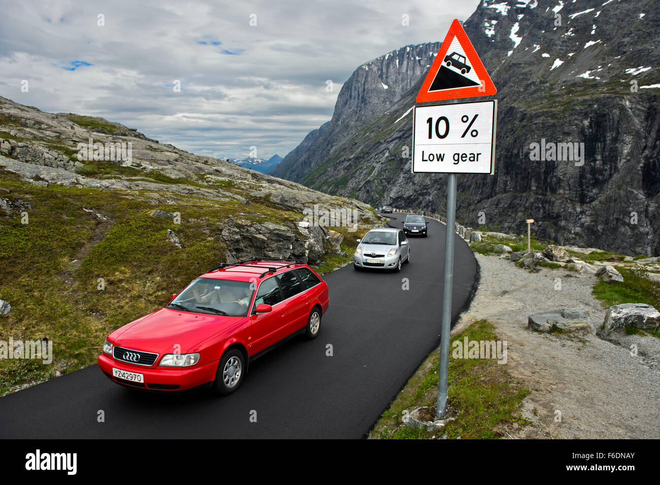 Cars passing a road sign warning of a steep road grade on the Trollstigen National Tourist Route, Møre og Romsdal, - Stock Image