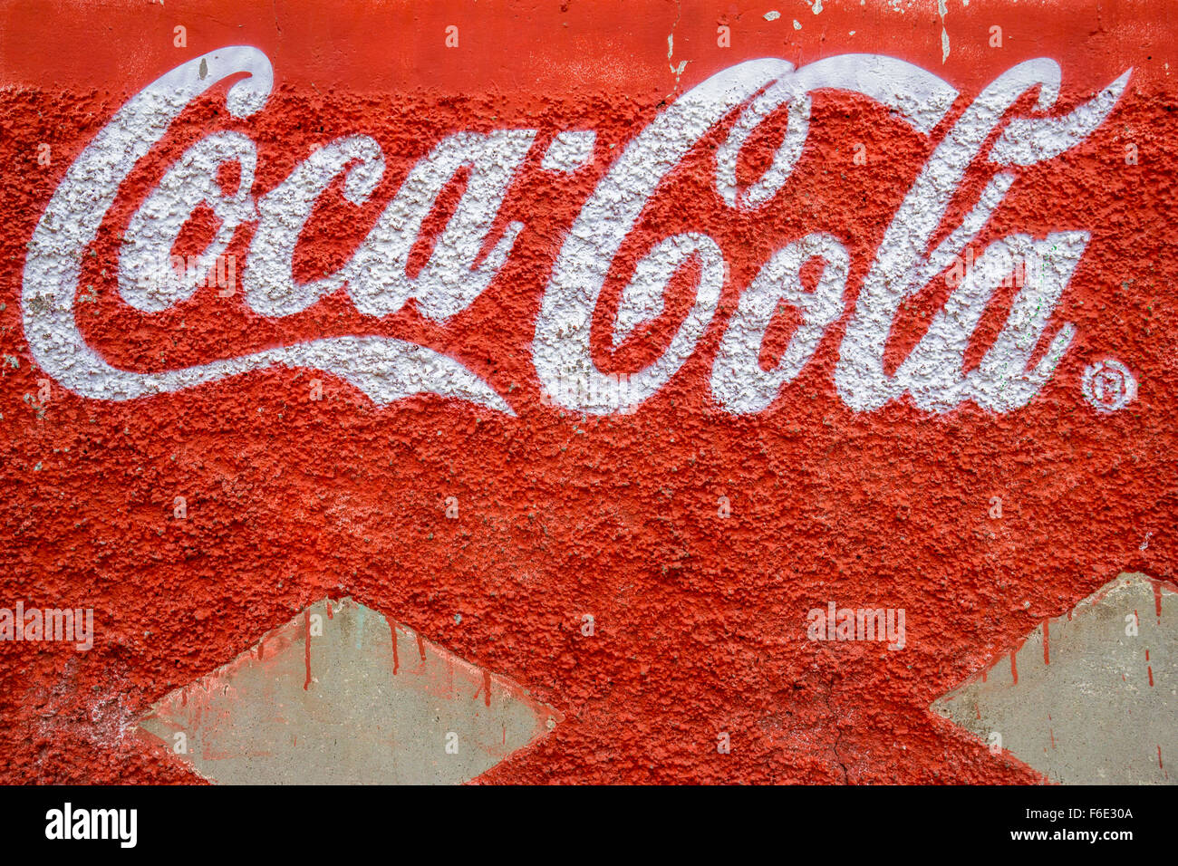 LIMA, PERU - OCTOBER 10, 2014 : Coca Cola trademark letters written on a rough red wall, seen in Lima, Peru - Stock Image