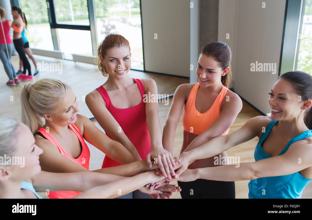 group of women with hands on top in gym Stock Photo